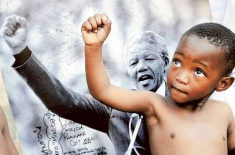 A young member of the Maitibolo Cultural Troupe, who came to dance for well-wishers in honour of Nelson Mandela, poses for well-wishers in front of a placard of Mandela, outside the entrance to the Mediclinic Heart Hospital where former South African President Nelson Mandela is being treated in Pretoria, South Africa Photo: AP