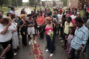 Mourning mother: Lesley McSpadden, center, drops rose petals on the blood stains from her 18-year-old son Michael Brown who was shot and killed by police in the middle of the street in Ferguson.