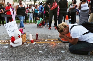 Meghan O'Donnell, 29, from St. Louis, prays at the spot where Michael Brown was killed the previous afternoon, Sunday evening, Aug. 10, 2014, in Ferguson, Mo. Police said Brown, who was unarmed, was fatally shot Saturday in a scuffle with an officer.  AP Photo/St. Louis Post-Dispatch, J.B. Forbes