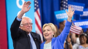 Presumptive Democratic presidential candidate Hillary Clinton and Bernie Sanders wave after speaking at a rally in Portsmouth, N.H. earlier this month